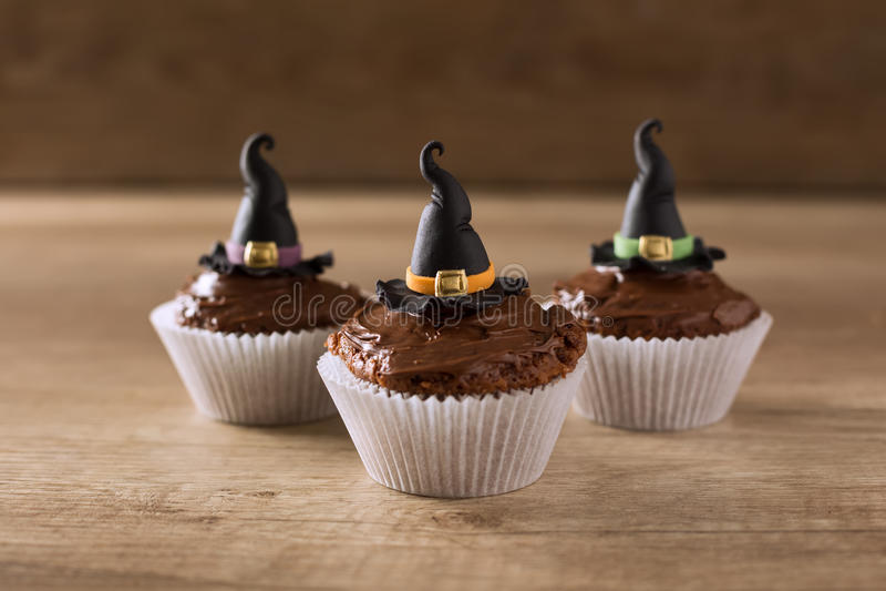 Tres cupkaces con el día de fiesta de Halloween del sombrero de la bruja imagenes de archivo