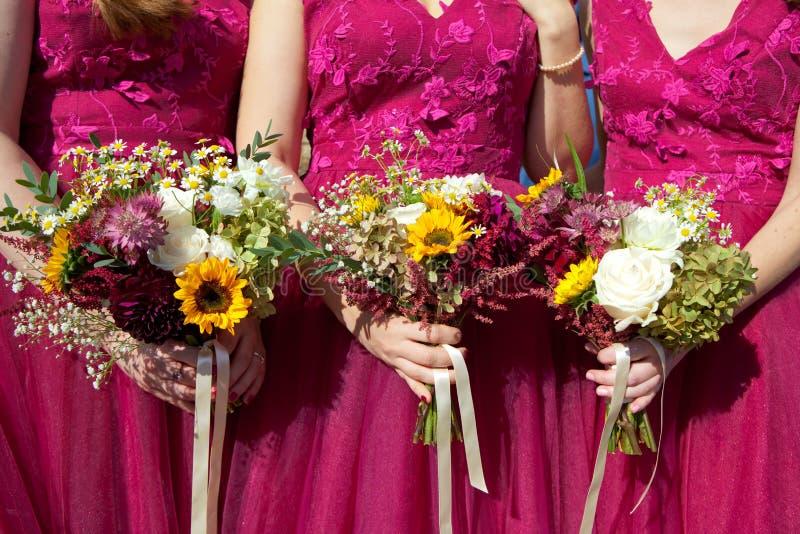 Tres damas de honor en vestidos del cordón de la lila con los ramos de flores frescas, foco selectivo imagen de archivo libre de regalías