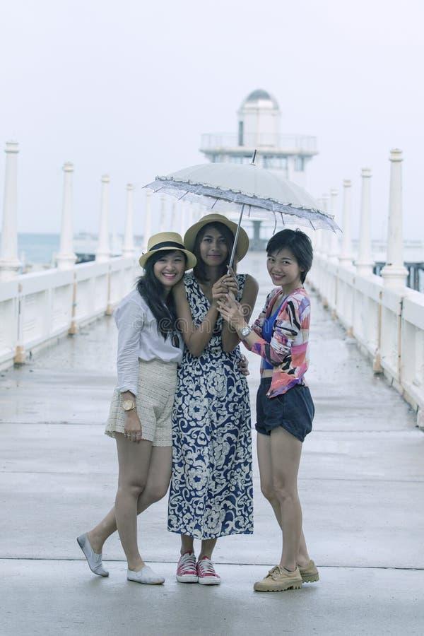 Tres de un amigo asiático más joven de la mujer debajo de un paraguas en lluvioso imágenes de archivo libres de regalías
