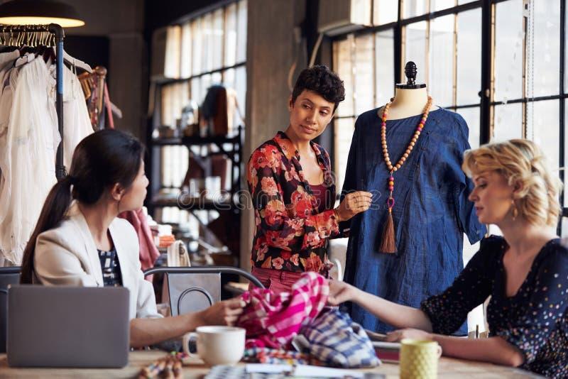 Tres diseñadores de moda en la reunión que discuten la ropa fotos de archivo