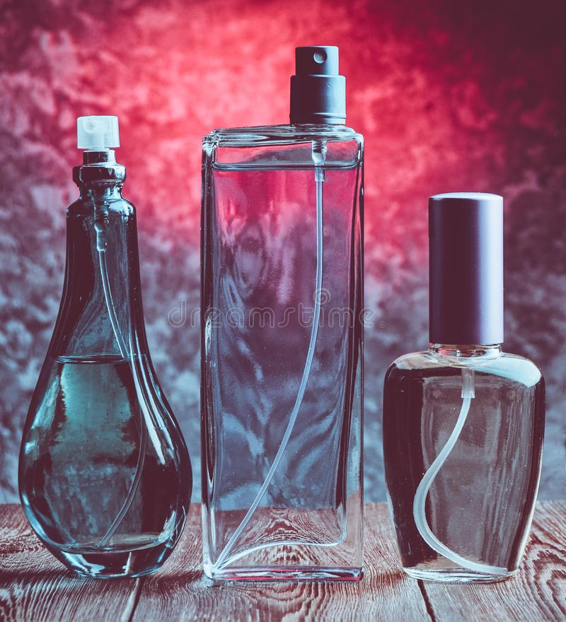 Tres diversas botellas de perfume en un estante de madera foto de archivo