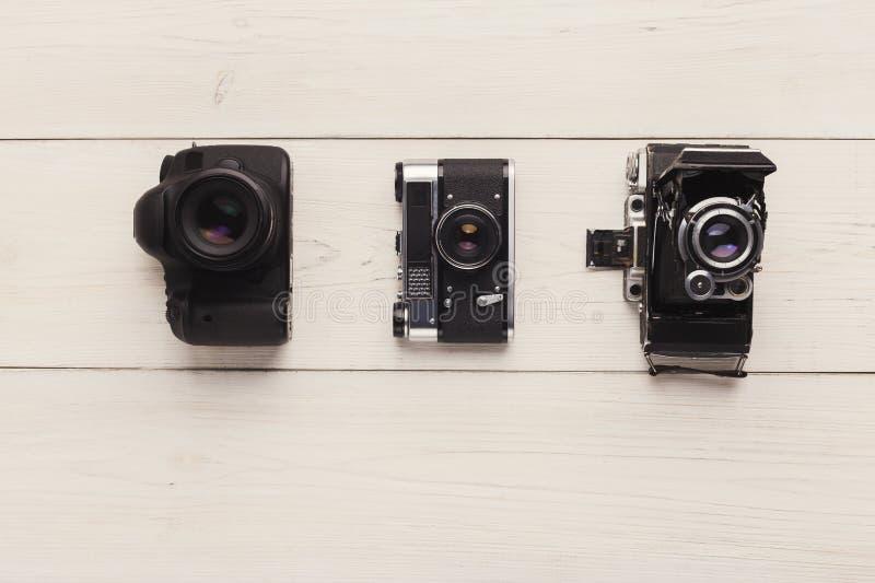 Tres diversas cámaras en la tabla blanca fotografía de archivo