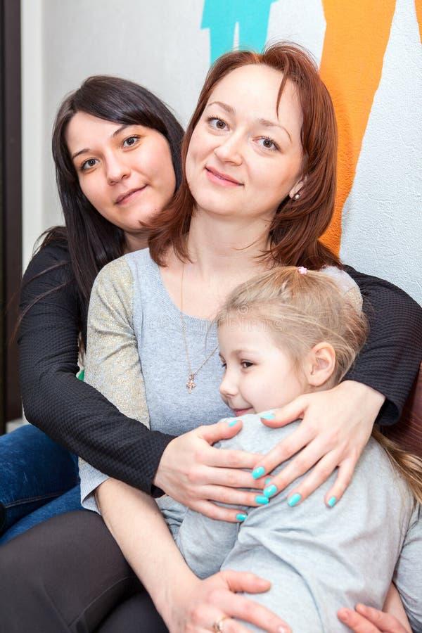 Tres diversas edades de las hermanas felices que abrazan junto imagen de archivo