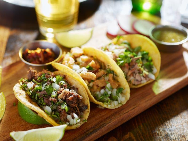 Tres diversos tacos mexicanos de la calle con carne de vaca y cerdo foto de archivo