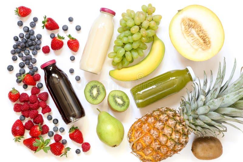 Tres diversos tipos de jugos o de smoothies frescos en las botellas y los ingredientes aislados en el fondo blanco imágenes de archivo libres de regalías