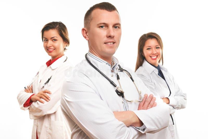 Tres doctores jovenes hermosos y enfermera fotos de archivo