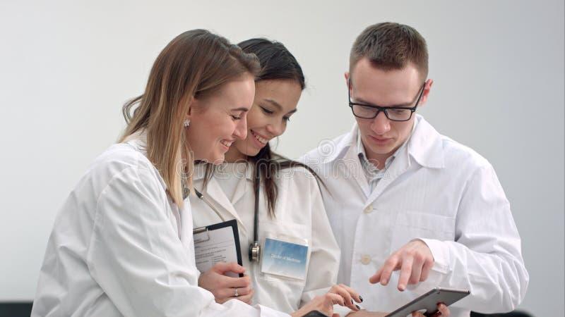Tres doctores sonrientes que discuten la radiografía mientras que usa la tableta imagenes de archivo