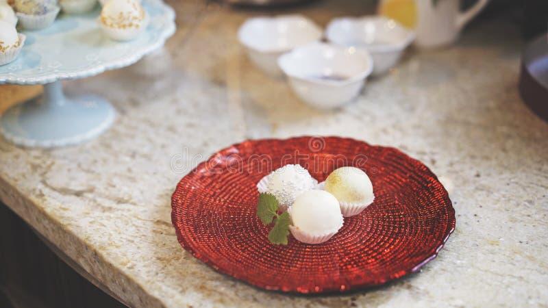 Tres dulces están en una placa de cristal roja con un pedazo de menta imagen de archivo