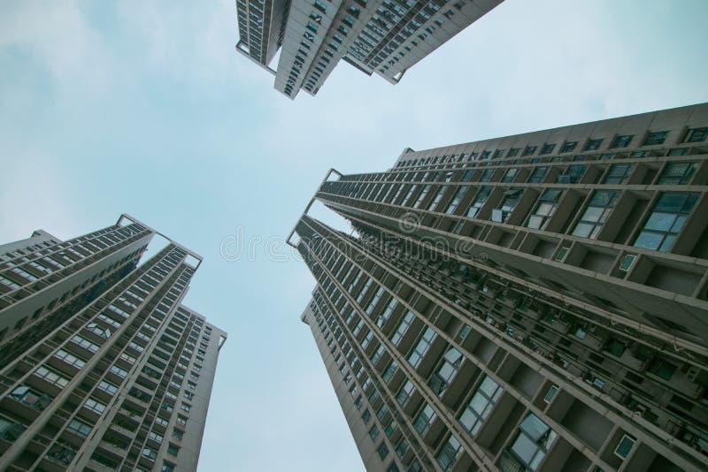 Tres edificios altos que se van para arriba a largo plazo contra la perspectiva del cielo azul, el área residencial de la ciudad  imagen de archivo