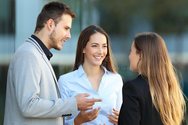 Tres ejecutivos que hablan en la calle imagenes de archivo