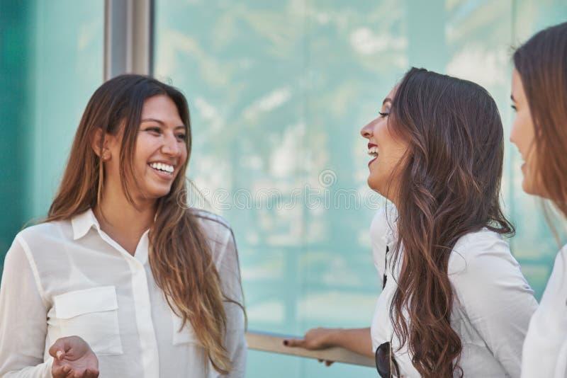 Tres empresarias jovenes que ríen junto afuera fotografía de archivo
