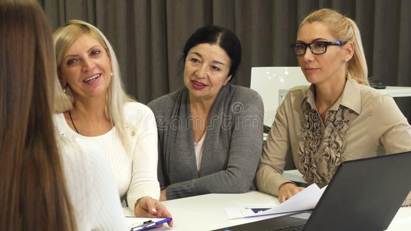 Tres empresarias que se entrevistan con al nuevo empleado para el trabajo en la oficina fotografía de archivo libre de regalías