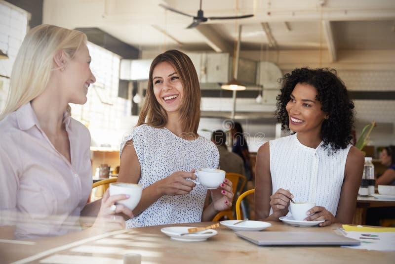 Tres empresarias se encuentran en la cafetería tirada a través de ventana fotos de archivo libres de regalías