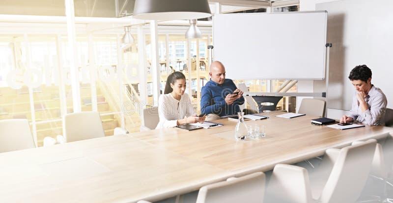 Tres empresarios eclécticos que miran sus teléfonos imagen de archivo