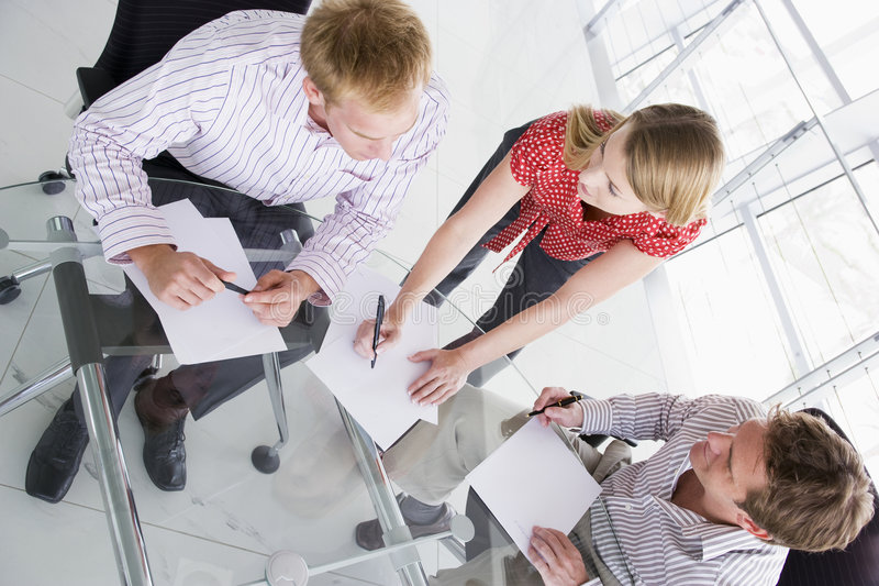 Tres empresarios en la sala de reunión con papeleo imágenes de archivo libres de regalías
