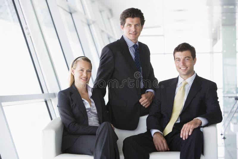 Tres empresarios que se sientan en pasillo de la oficina fotos de archivo libres de regalías
