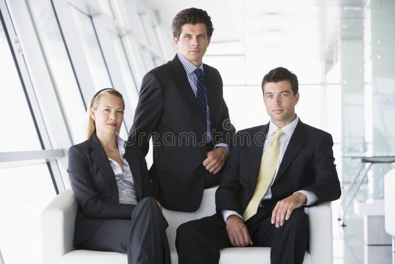 Tres empresarios que se sientan en pasillo de la oficina foto de archivo libre de regalías
