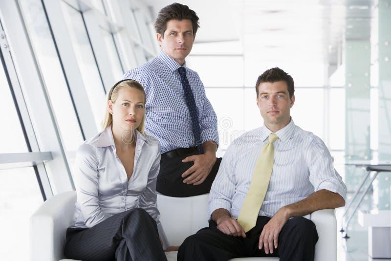 Tres empresarios que se sientan en pasillo de la oficina imagen de archivo