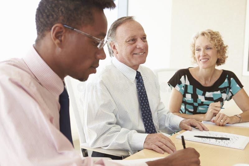 Tres empresarios que tienen reunión en la sala de reunión fotos de archivo