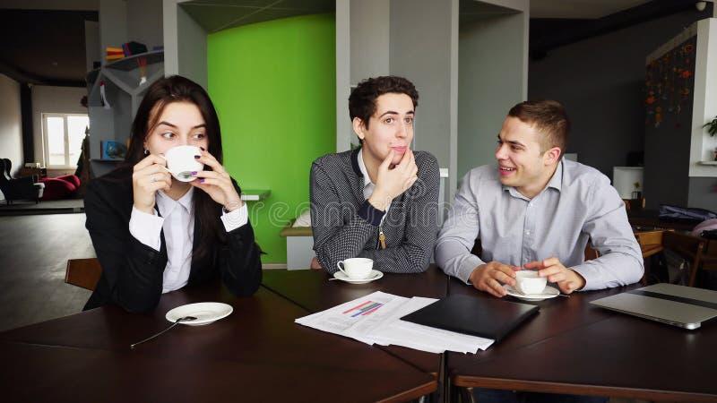 Tres encargados jovenes, mujer y dos hombres charlando y descansando para fotografía de archivo libre de regalías