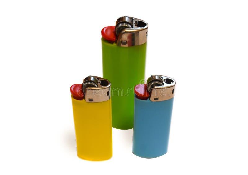 Tres encendedores coloridos aislados en el fondo blanco con el espacio de la copia imagen de archivo libre de regalías