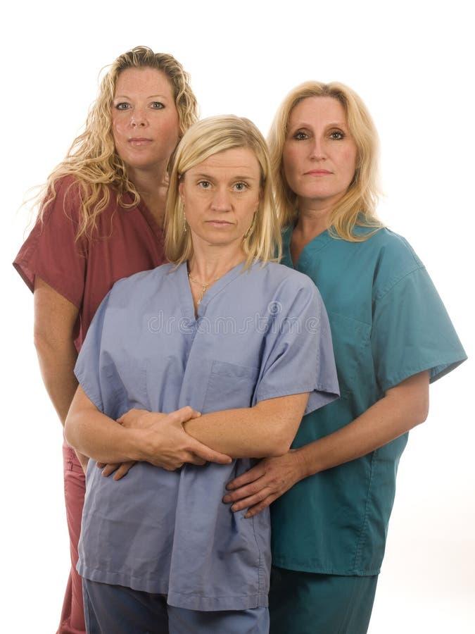 Tres enfermeras en médico friegan la ropa imagen de archivo libre de regalías