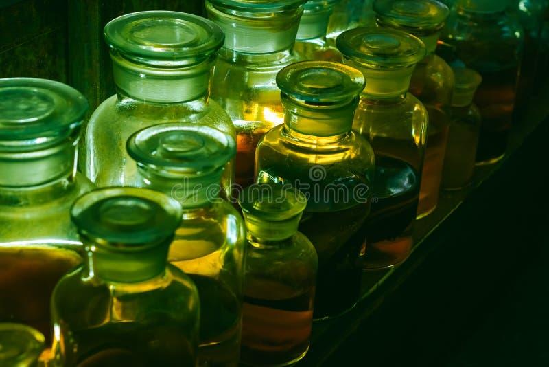 Tres envases de cristal con las hojas coloridas del líquido y de la caída del limo Concepto mágico de la brujería de Eve de Hallo imagen de archivo