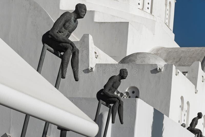 Tres esculturas del observador con la catedral metropolitana ortodoxa en Fira, Santorini, Grecia imagenes de archivo
