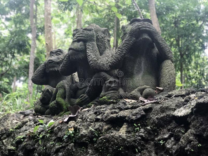 Tres estatuas de los monos que tienen diversos posts camboya imagen de archivo