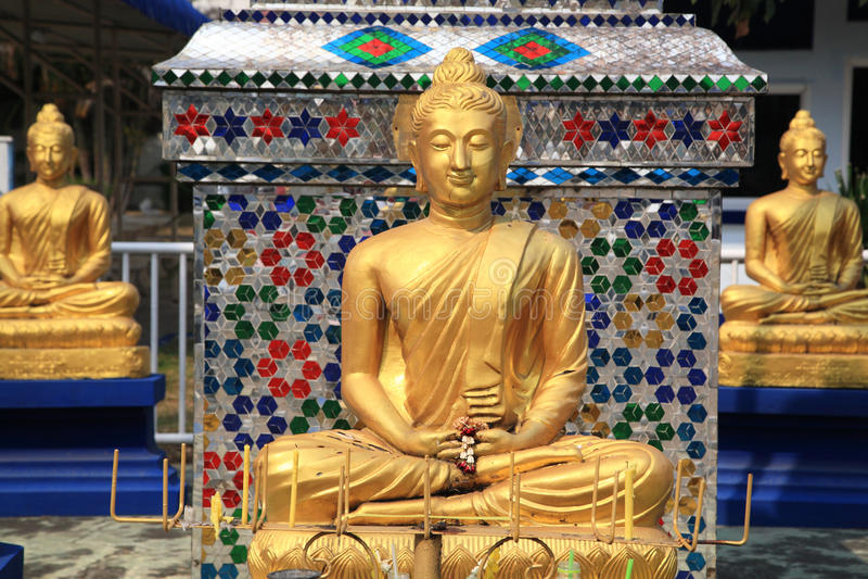 Tres estatuas de oro de Buda en el templo tailandés foto de archivo