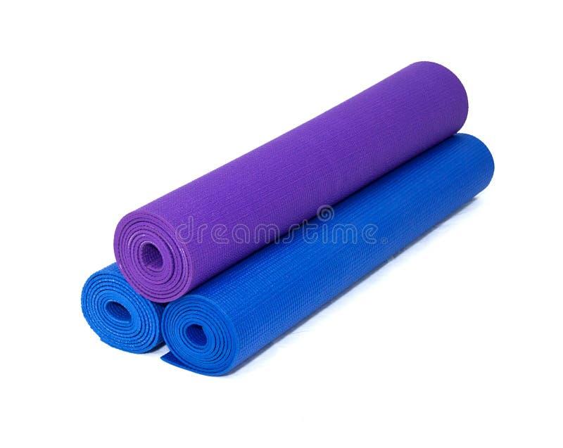 Tres esteras rodadas del ejercicio de la yoga empiladas en blanco fotos de archivo
