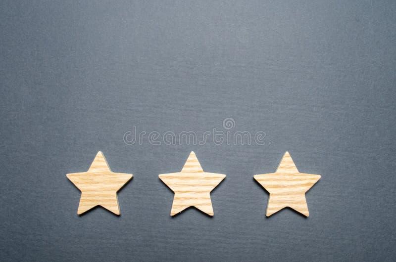 Tres estrellas de madera en un fondo gris El concepto de calidad y de prestigio De alta calidad y confiabilidad, aceptación unive foto de archivo