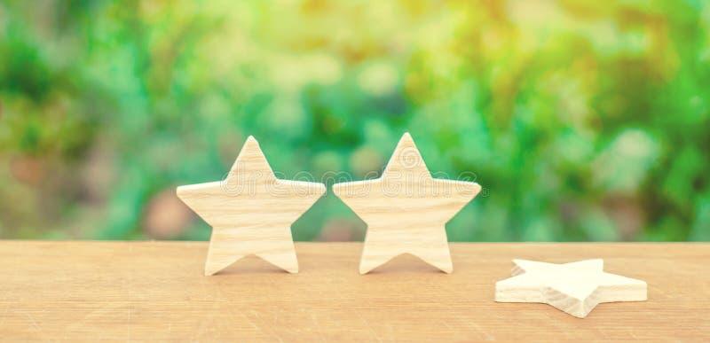 Tres estrellas, una estrella cayeron El concepto de una caída en el grado y la calidad Privación de la tercera estrella Obsevacio imagen de archivo libre de regalías