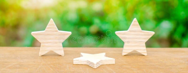 Tres estrellas, una estrella cayeron El concepto de una caída en el grado y la calidad Privación de la tercera estrella Obsevacio fotos de archivo libres de regalías