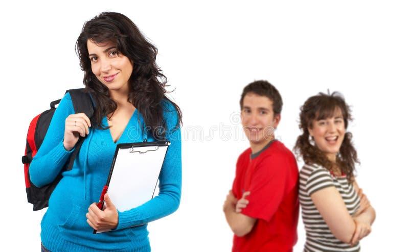 Tres estudiantes con los libros y los morrales fotos de archivo