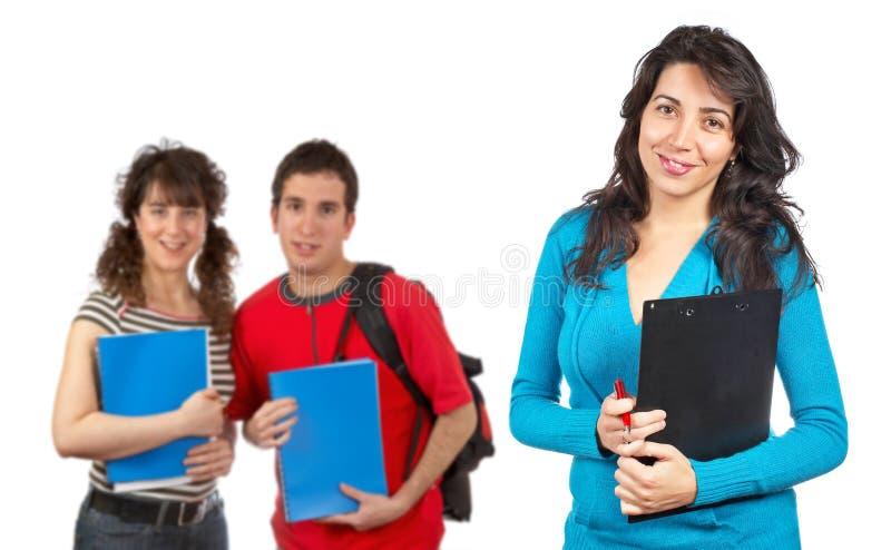 Tres estudiantes con los libros y los morrales fotografía de archivo