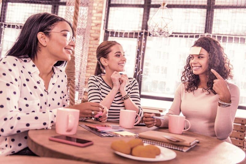 Tres estudiantes creativos que juegan el té de consumición del juego de palabra y que comen las galletas foto de archivo