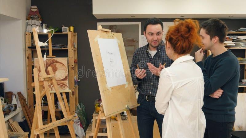 Tres estudiantes de arte alegres que discuten la pintura en estudio imagenes de archivo