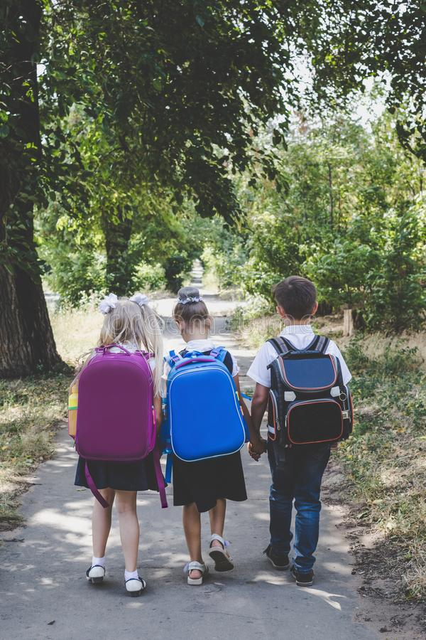 Tres estudiantes de la escuela primaria con las mochilas fotografía de archivo