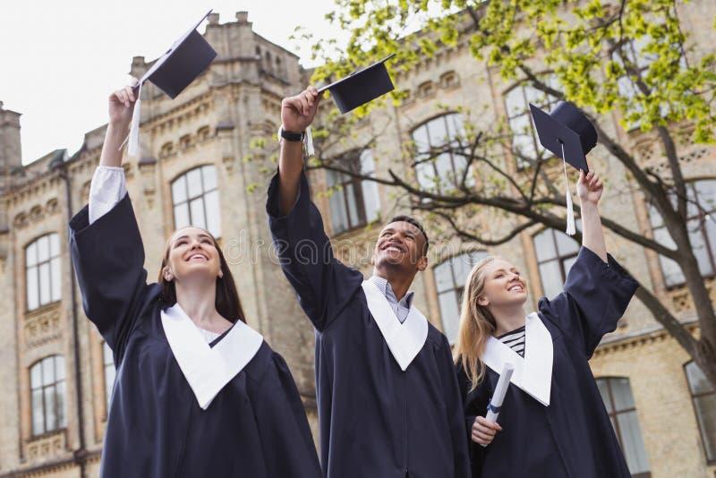 Tres estudiantes felices que lanzan sus birretes en el aire foto de archivo libre de regalías