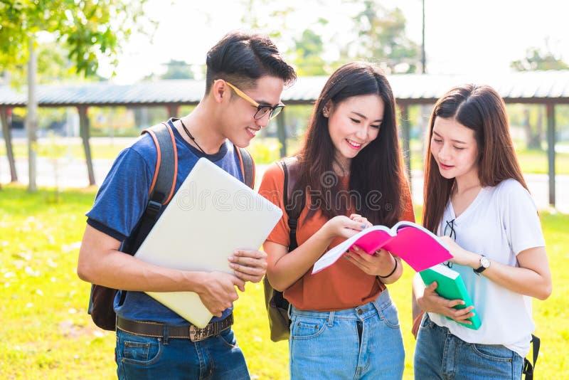 Tres estudiantes jovenes asiáticos del campus disfrutan de abucheo de las clases particulares y de la lectura foto de archivo