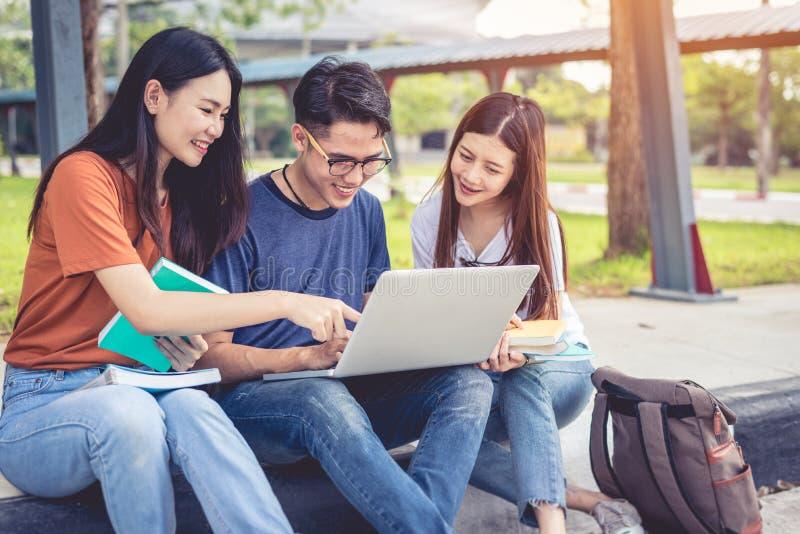 Tres estudiantes jovenes asiáticos del campus disfrutan de abucheo de las clases particulares y de la lectura fotos de archivo