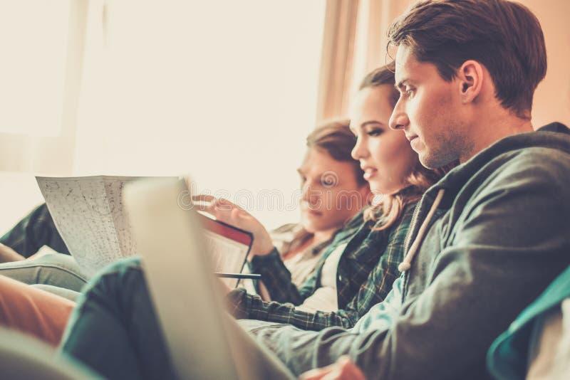 Tres estudiantes jovenes que se preparan para los exámenes imagen de archivo libre de regalías