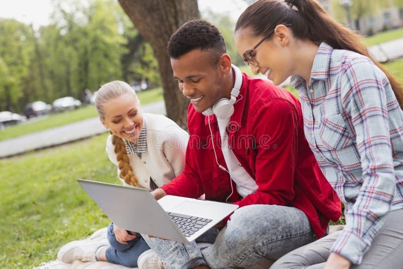 Tres estudiantes que charlan vía Skype con su amigo imágenes de archivo libres de regalías