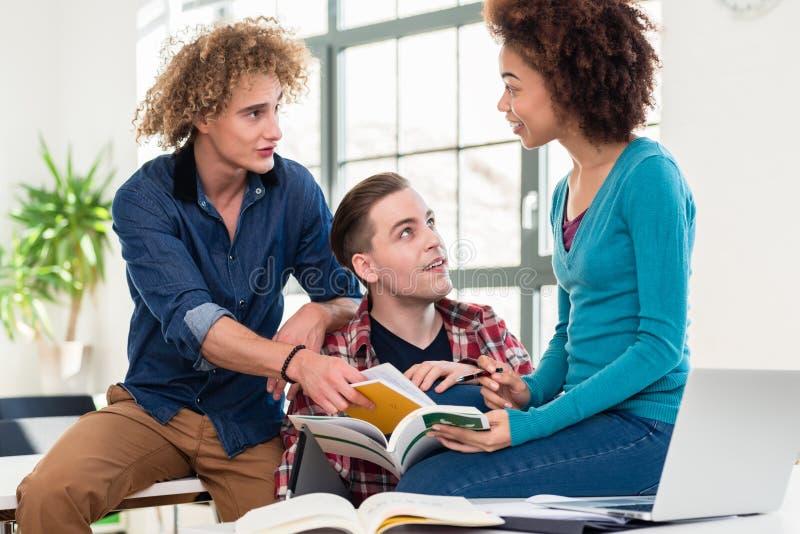 Tres estudiantes que comparan la información a partir de diverso libro de texto el dos imagen de archivo
