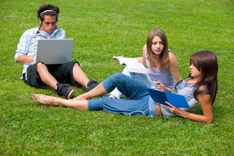 Tres estudiantes que estudian al aire libre imagenes de archivo