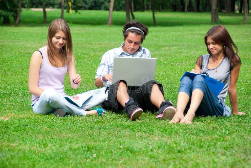 Tres estudiantes que estudian al aire libre foto de archivo