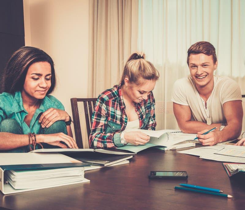 Tres estudiantes que se preparan para los exámenes en el interior casero fotografía de archivo