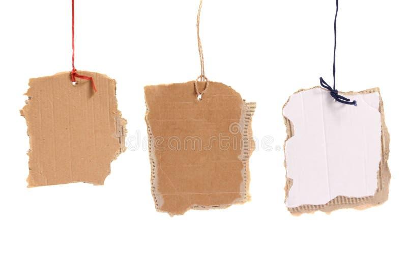 Tres etiquetas de la cartulina que cuelgan en el fondo blanco imágenes de archivo libres de regalías