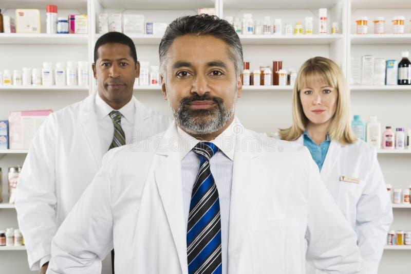 Tres farmacéuticos confiados que se colocan en la farmacia fotos de archivo libres de regalías